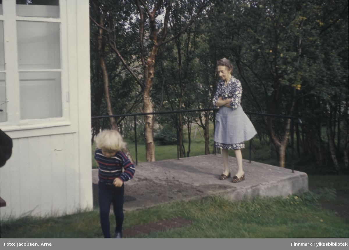 Bestemor Sigrid Nakken og Arne Nakken. Sigrid har mønstret skjørt og lik overdel med et forkle på. På beina har hun tøfler og står på en trapp. Trappa har betongdekke og sortmalt metallgelender og det er gressplen rundt. Arne løper mot fotografen og har mørke bukser og stripete genser på seg. Hjørnet av en lysmalt bygning og vindu med sprosser til venstre. Det er mye trær med løv på området.