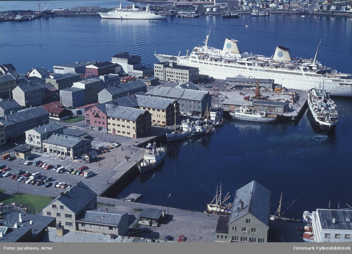 """Hammerfest havn en flott sommerdag, i 1966 eller 1967*.  Nede til venstre ser man Rådhusplassen med en del biler parkert.  Bygget nederst med røstet mot kamera er Finnmarksbo.  Nissengården og Televerksbygget, nå biblioteket sees midt i bildet.  Et skip ligger ved Bangkaia og ved Rådhuskaia ligger FFR-båten """"Tamsøy"""".  Ved Nissenkaia ligger en liten klynge båter.  Ved godsterminalen ligger FFR-båten """"Rypøy"""" ikke langt fra  Hurtigruta""""Lofoten"""". Ved Dampskipskaia/Hurtigrutekaia ligger et turistskip, SAL`s """"Kungsholm"""".  Foran baugen ligger FFRs hovedadministrasjon og Nord-Norges Salgslag.  På andre siden av havna ligger bydelen Fuglenes.  Turistskipet er israelske """"Shalom"""" fra 1964, det ligger ved kai  på Fuglenesodden. Foran baugen sees båtslippen på Fuglenesodden.  Noen småbåter er ute på havna og Hammerfest vidregående skole ses øverst bak hekken på turistskipet.  *Iflg. vår informant ble turistskipet """"Shalom"""" høsten 1967 solgt til Deutsche Atlantic Linie, Hamburg og fikk nytt navn: """"Hanseatic"""". Bildet kan derfor dateres til sommeren 1966 eller 1967, altså før skipet ble solgt videre."""