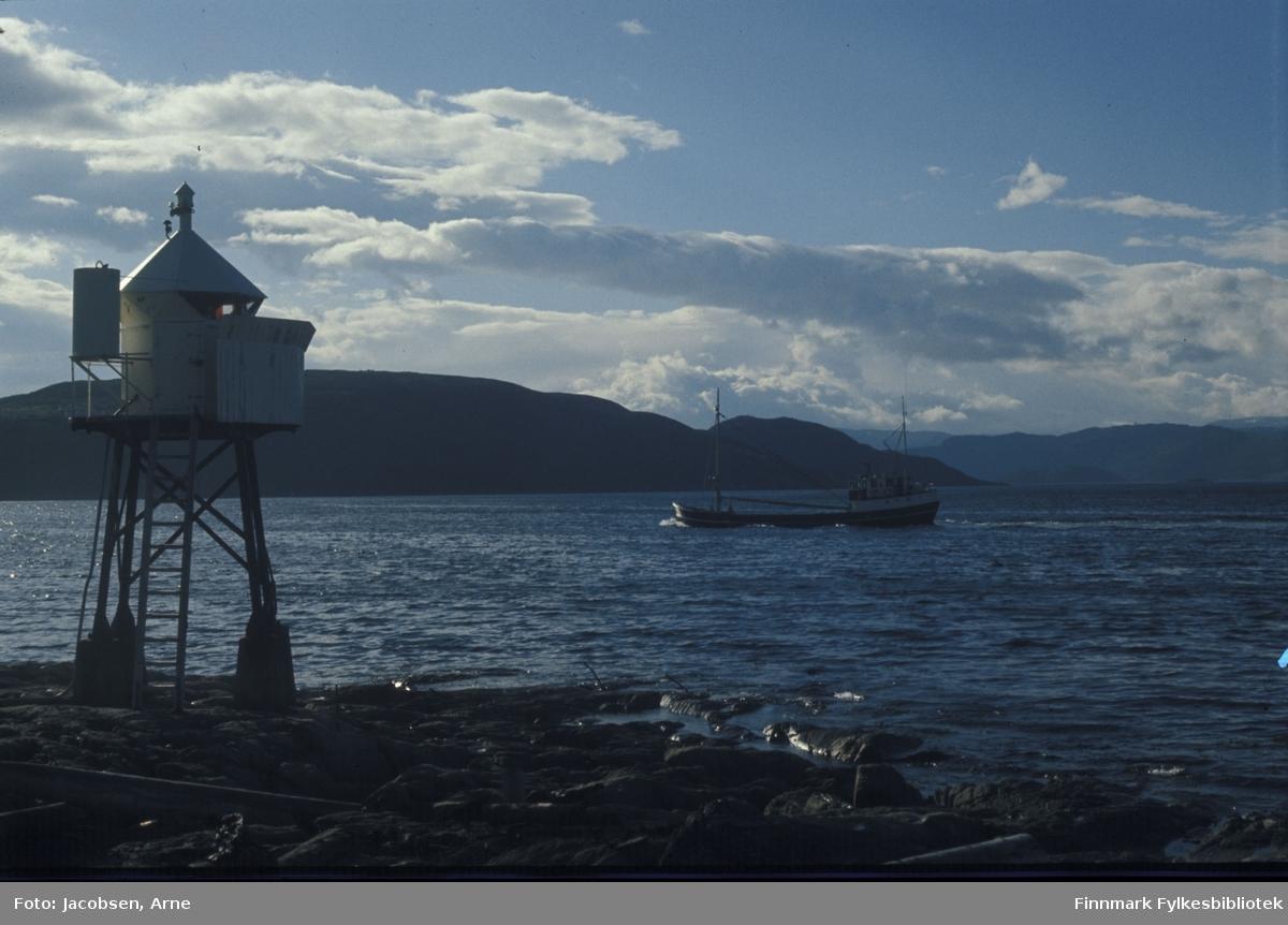 Fyrlykta på Fuglenesodden i solskinn. En fraktskute er på vei inn til Hammerfest. Rypklubben bak fyrlykta og båten, Seiland mer diffust til høyre i bildet. Med bare noen skyer og lite vind ser det ut til å være en fin sommerdag.
