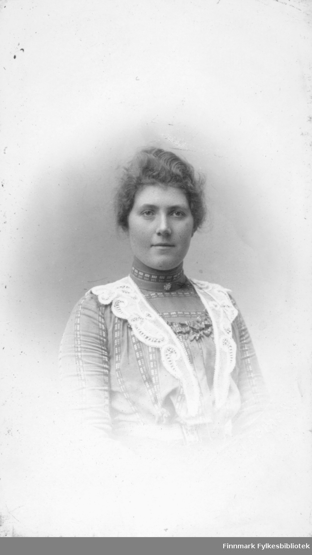 Portrett av ukjent kvinne. På bildet har hun en høyhalset bluse eller kjole på seg. Over skuldrene har hun hengende en lang blondekrave
