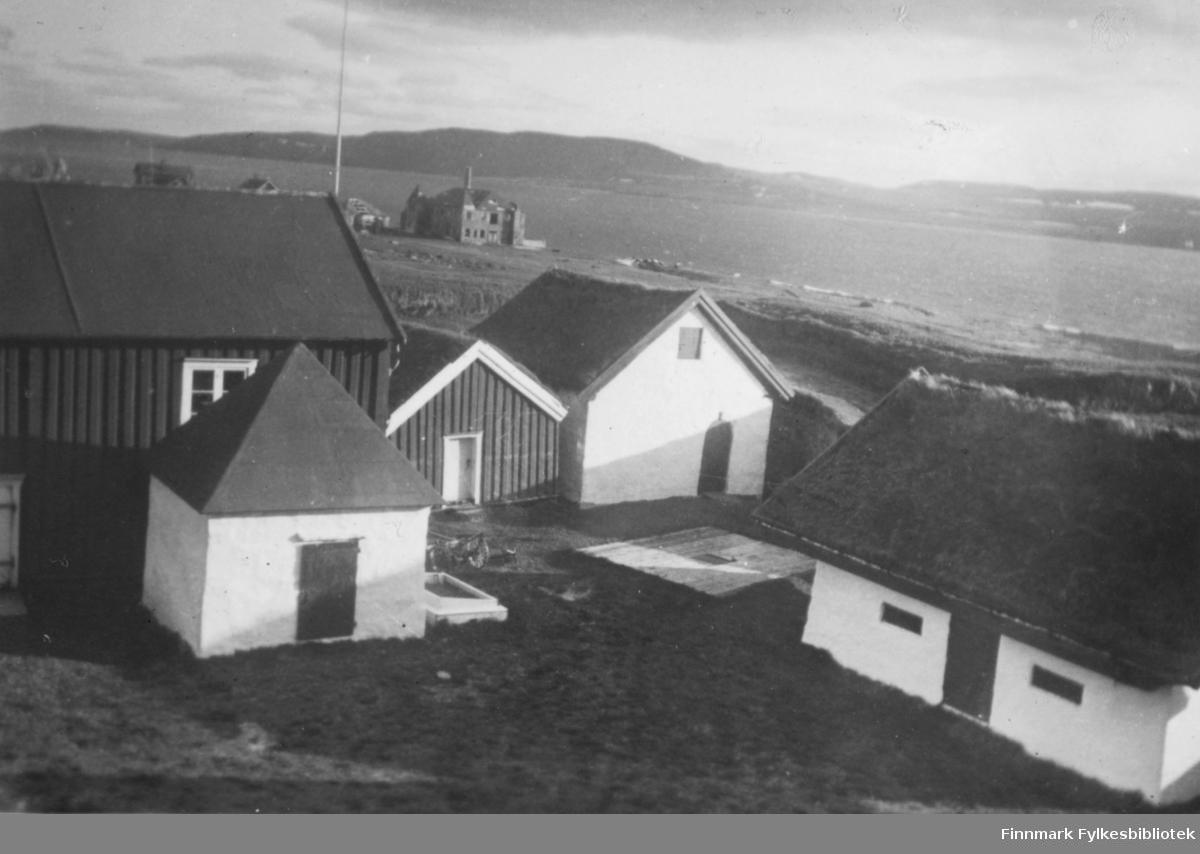 Fotografi fra Vardøhus Festning. Innenfor vollen ser vi fem bygninger. Et lite hvit murhus med  et spiss tak. En  stor mørk trebygning, og et mindre med torvtak. Det er også to hvite murbygninger med torvtak. Bak i bildet ser vi flere hus som ligger ned mot fjæra. Det er fjell på andre siden av sjøen