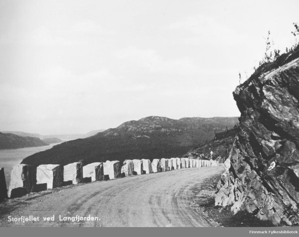Postkort fra Storfjellet ved Langfjorden. På fotografiet som er tatt i en sving på veien, kan man se utover langfjorden og fjell i området. Langs grusveien på venstre side er det satt store steiner langsetter som et autovern. På øversiden av veien er det fjell