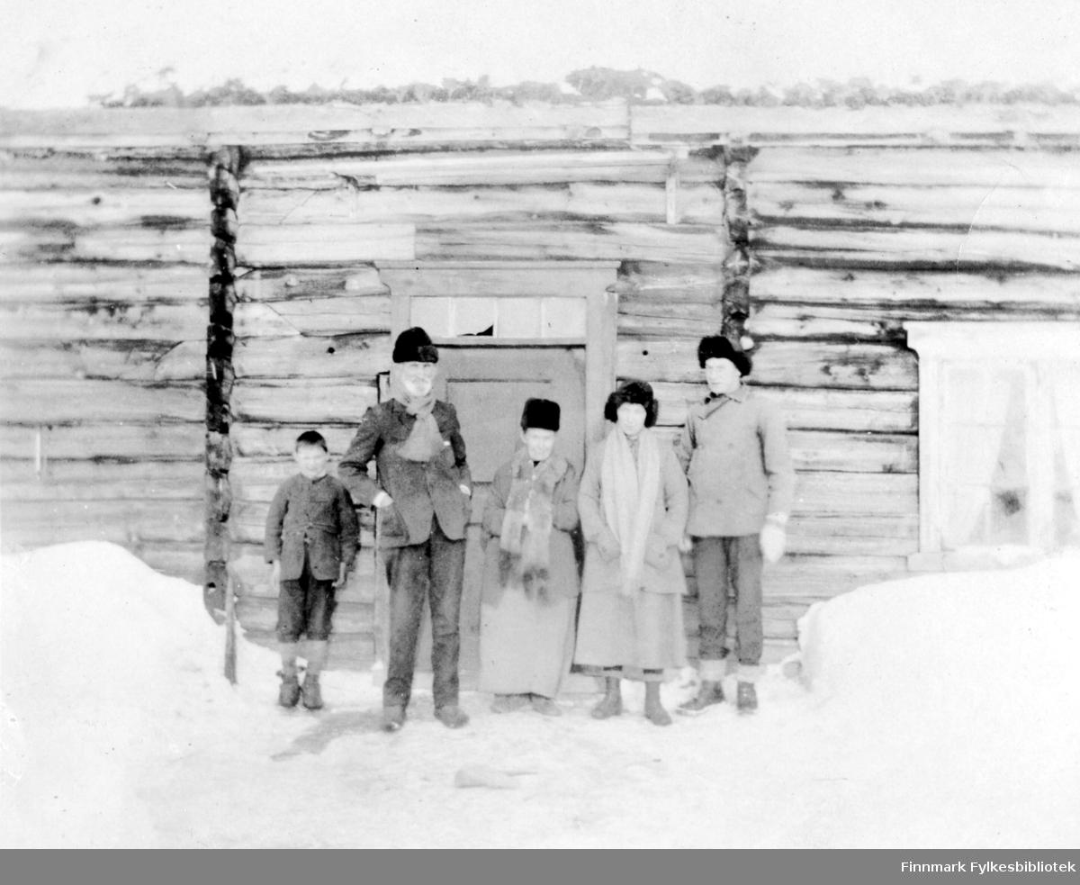 Fotografi av en gutt og fire menn som står utenfor en laftet tømmerbygning. Mannen som står som nummer to fra venstre har hvitt skjegg. Bak mennene er det en dør med vinduer og brede trelister med utskjæringer. Vinduet til høyre har sprosser og  utskjæringer på listene. Det er snø på bakken, og mennene er vinterkledt. Alle har luer på hodet. Tre av mennene har skjerf rundt halsen