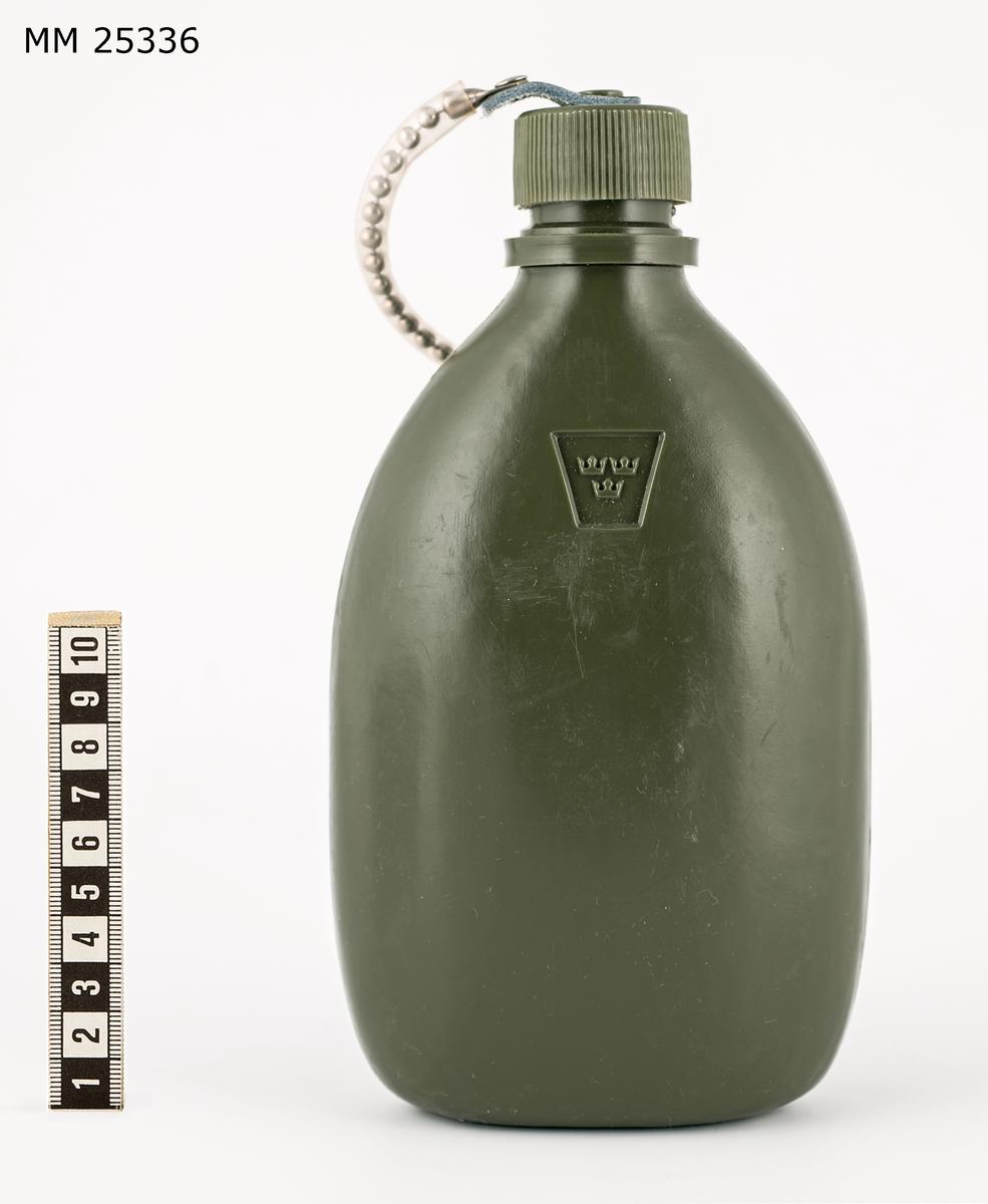 """Dricksflaskan 90. Flaska av grön plast med skruvlock av plast, lockfäste av plastbeklädd metallänk samt fästring och läderrem med fästbeslag av aluminium. Märkt med kronstämpel i relief. I botten även märkt: """"Mellerud""""."""