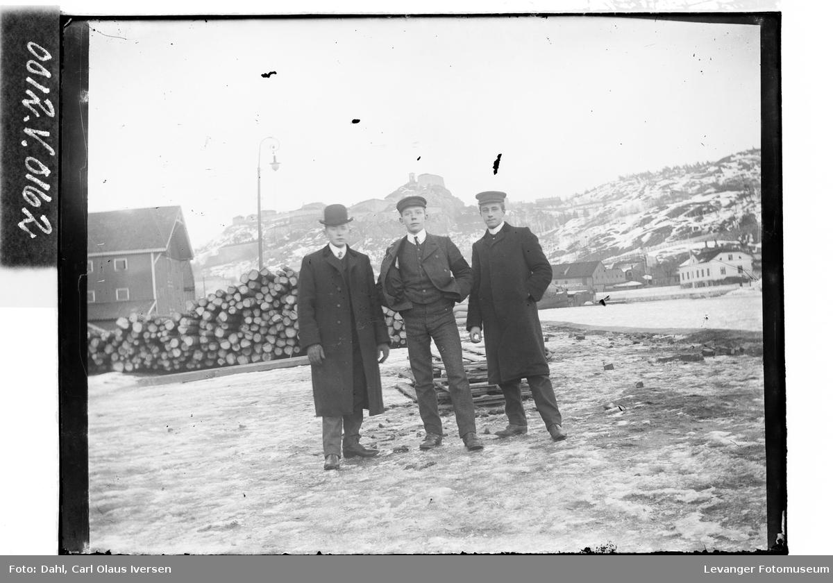 Tre menn med Slottsfjellet i bakgrunnen