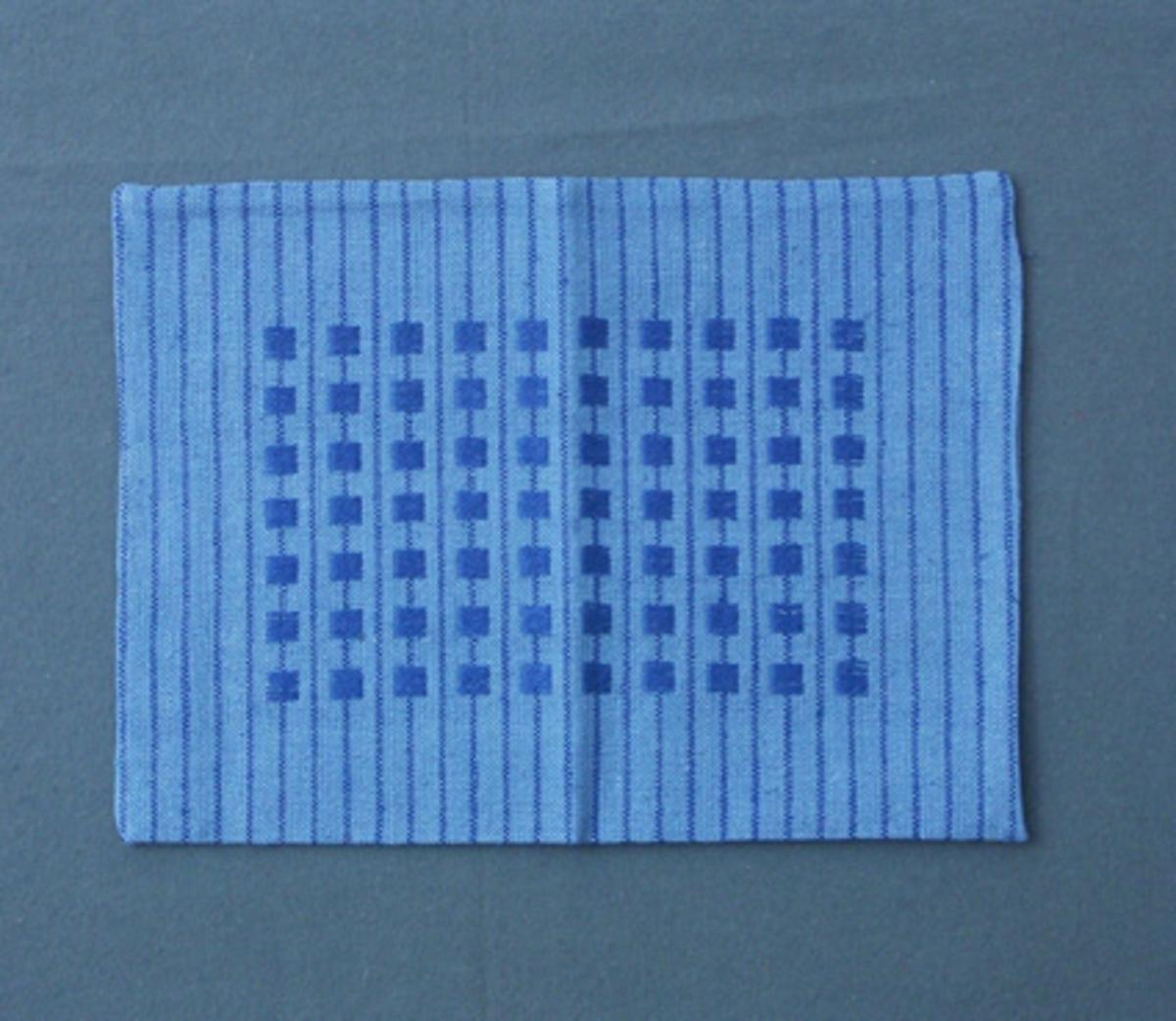 Kuddvar vävt i tuskaft med mönster i plattväv, eller tärningsväv som det kallats i tidigare inventering, på randig botten.