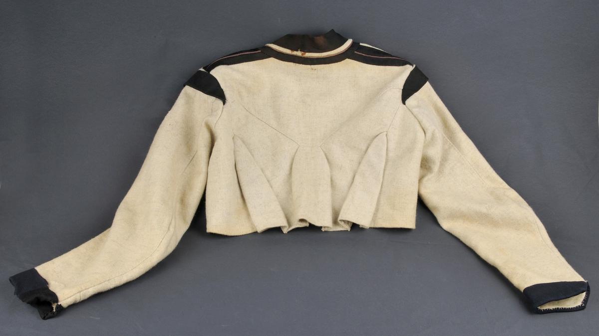 Trøye av kvitt og gråmelert vadmål. Besetning av svart klede. Biser i skulder og kragesaum av fiolett klede. Venstre fremstykke har lomme av linlerret på vranga. Tosaumserme med bryning mot skulder. Sytråd: grov lintråd - samansydd med attersting.  Sømromet i øverste del av ryggen er bretta oppover og sydd til med kastesting.  I kilane er begge saumane lagde til kvarandre og sauma saman med kastesting.  Kilane får dermed ei klokkelignande form på retta.  Klokka i ryggen blir halden saman på vranga med to mellomstykker av vadmål.  I olbogesaumen er saummonnet lagt oppover og sydd ned.  I framsaum er saumrommet laust.  På skulder er fram- og bakstykke sydde saman med både besetning og biser under eitt. og alle 5 laga er kasta over med kastesting uten å vera sydde ned til bolen.