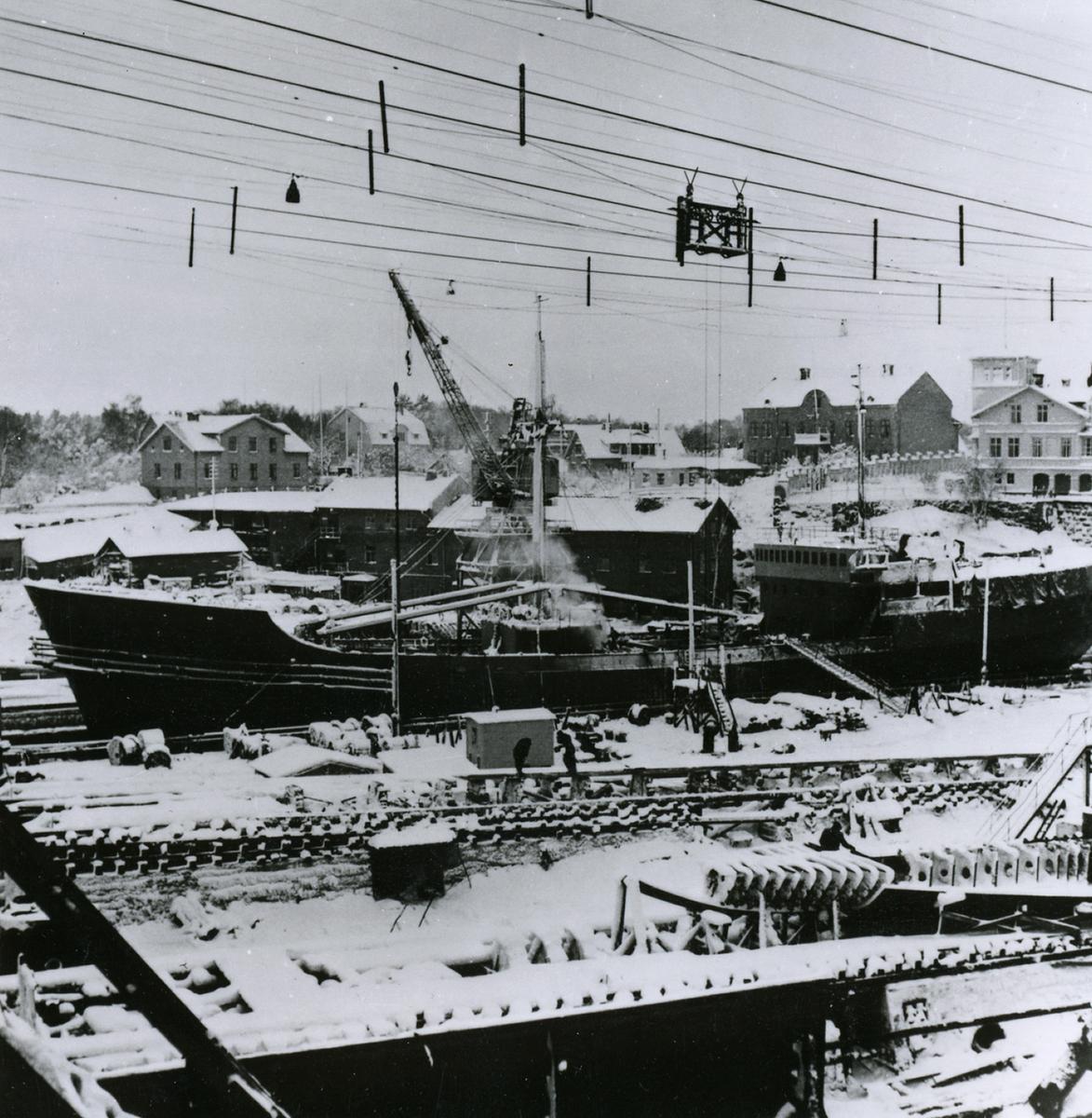 Oskarshamns varv. I dockan ligger kylmotorfartyget ÄELNOGRAD, på bädd kylmotorfartygen POLESK och MAGADAN, den 23.12.1955 efter snöfall.