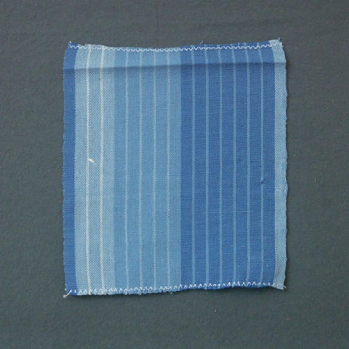 Blårandigt prov till gardin vävd i tuskaft med bomullsgarn i varp och inslag