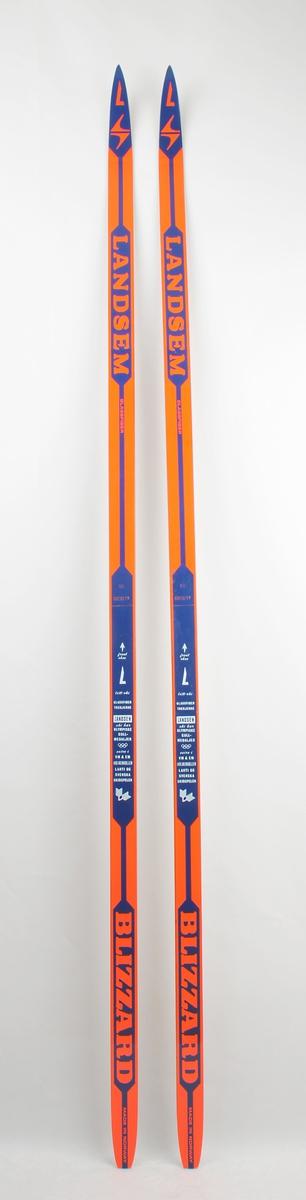 Langrennski laga av glasfiber, plastsåle. Oransje overside med blå dekorstripe.