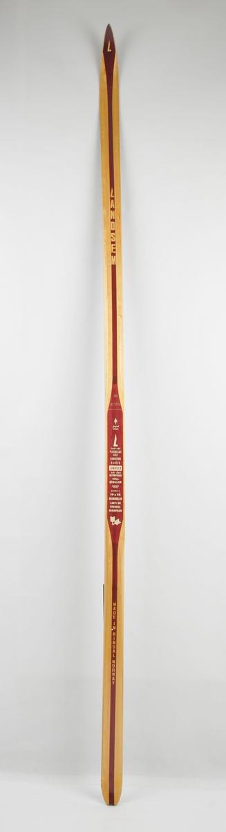 Langrennski laga av tre. Trekvit overflate, med brun dekorstripe midt på. Balsakjerne, plastbelagt bjørkesåle. Samme skitype som Magne Myrmo bruka då han vann i VM i Falun i 1974 (ref Holtskog).