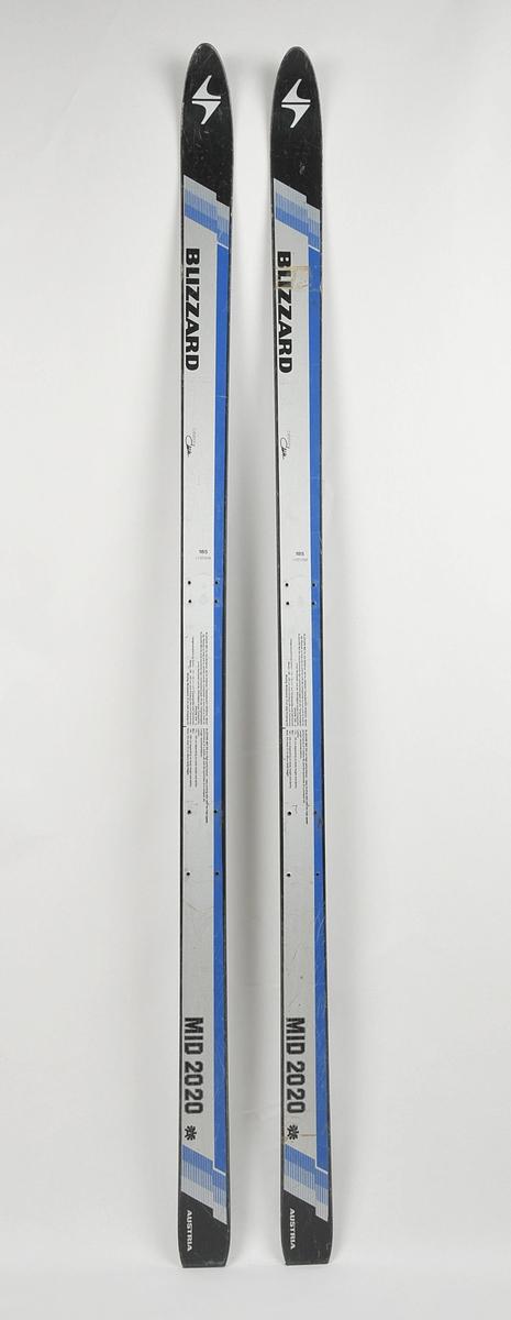 Alpinski laga av glasfiber. Sølv og svart overside med blå dekor,  blå plastsåle med stålkantar. Det har vore bora hol til bindingar.