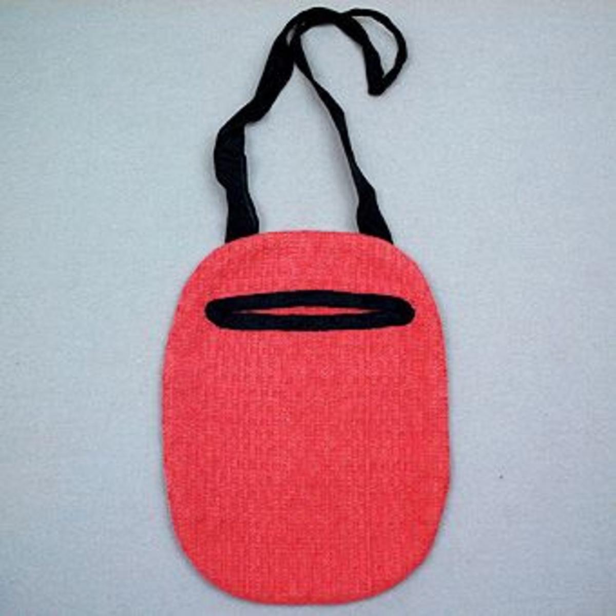 Kjolsäck till Sunnerbodräkt sydd i rosa daldrällstyg, sammat tyg har använts till  Sunnerbodräktens livstycken. Kjolsäckens öppning är kantad med svart ripsband, troligen av siden, som också använts till handtaget.