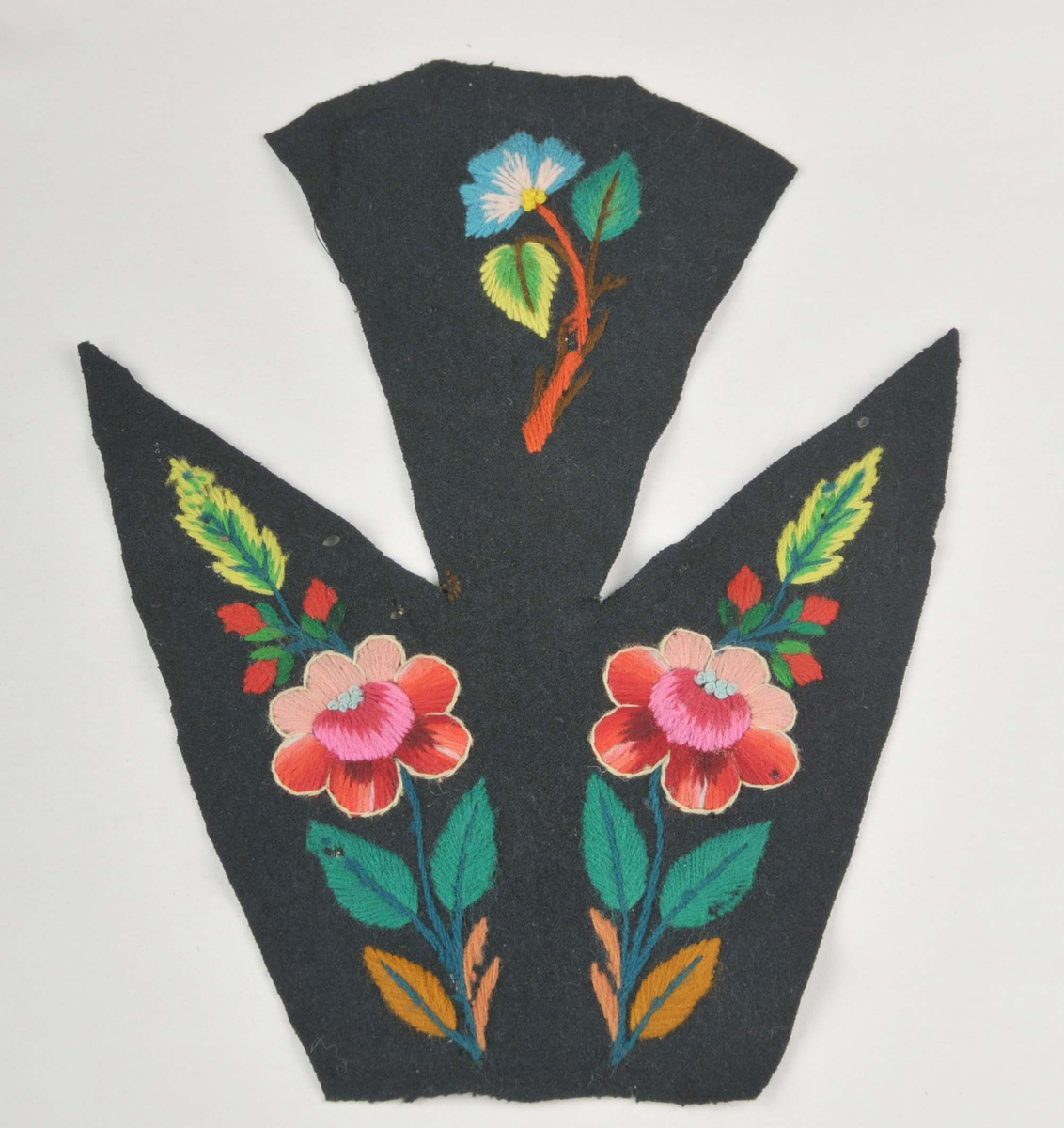 Broderi på svart klede, del av bakstykke til eit draktliv. Motivet er blomar og blad i sterke fargar. Blomene er kanta med kontursting i kvitt.