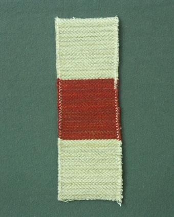 Möbeltygsprov i rött och naturvitt vävt i korskypert med bomullsgarn i varp och lin- och ullgarn i inslag.
