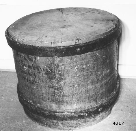 """Roderstock, del därav. Cylindrisk och gråmålad. Bandad med 2 stycken järnband. Märkt med svart: """"Har tillhört skeppet Skandinaviens Rorstock år 1830."""" Har tillhört linjeskeppet Skandinavien, sjösatt på Karlskrona örlogsvarv 1860. Efter kassation har stocken använts såsom huggkubbe för rep och tross i tackelkammaren på örlogsvarvet."""