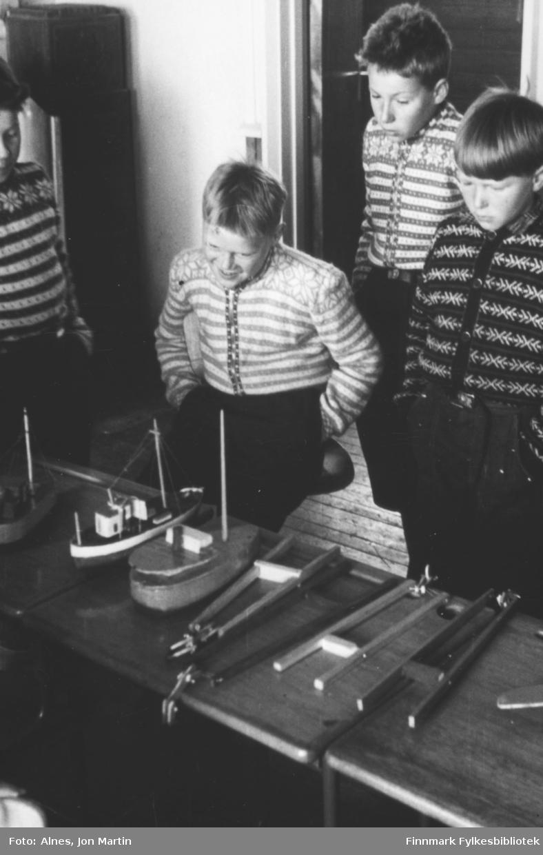 Fjerdeklassinger ved Øksfjord barneskole i 1954 står ved trebåter og annet de har laget i sløydtimene. Guttene fra venstre: Peder Roald Winterseth, Steinar Aslaksen, Gunnar Rydheim, Torfinn Kiil