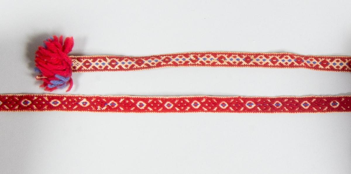 Kjolsäck till dräkt för kvinna från Bjursås socken, Dalarna. Modell med avskuret framstycke. Tillverkad av svart ylletyg, vadmal, med broderi utfört med ull- och silkegarn. Motiv: central stjärnblomma med uppstigande parvisa blad, på sidorna tre par med blommor. Konturer sydda med rött ullgarn: stjälksöm och sticksöm, utfyllnader med silkegarn i många färger: flätsöm och sticksöm. Framstycket fodrat med linnetyg, handvävt, tuskaft, bakstycke av samma tyg. Kantat runtom med rött diagonalvävt ylleband. I överkanten fastsytt ett handvävt band med plockat mönster i rött och lite blått på vit botten, avslutat i var ände med små tofsar av rött och blått ullgarn.