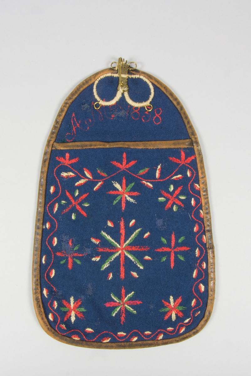 Kjolsäck till dräkt för kvinna från Nås socken, Dalarna. Modell med avskuret framstycke. Tillverkad av blått ylletyg, vävt i kypert, kanske handvävt. Broderad med ullgarner i flera färger, dominerande färg rött: sjtälksöm och plattsöm. Motiv: stjärnformade blommor, varje blomma i minst tre färger, längs kanten en slinga. På överstycket märkt: AMD 1838, vilket möjligen kan vara tillverkningsår på förlagan. Foder av fabriksvävt beige linnetyg, tuskaft. Kantad runtom med remsa av brunt skinn, samma skinn har använts till baksida. I överkanten fastsydd en stor hake tillverkad av mässingstråd.