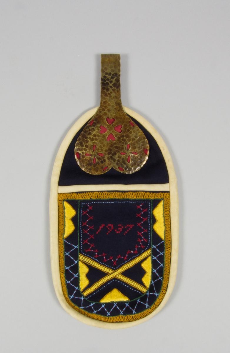 Kjolsäck till dräkt för kvinna från Idre socken, Dalarna. Modell med avskuret framstycke. Tillverkad av svart ylletyg, kläde, med broderi utfört med glansigt bomullsgarn i gult, brungult, rött, blått med flera färger: plattsöm, flätsöm, stjälksöm, korssöm, sticksöm. Motiv: ram sydd med flätsöm, i mitten oilka fält med broderi, sydd märkning 1937 syftar säkert på tillverkningsår. Kantat runtom med sämskskinn. Överstycke av svart kläde med fastsydd stor hake. Hakbeslaget har hamrad yta och stansade hål i blomformer, med rött kläde som underlägg. Foder av linnetyg, troligen fabriksvävt, tuskaft. Bakstycke av sämskskinn.