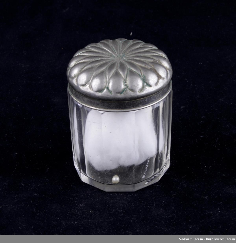 Glassbeholder med lokk av sølvplett. Inni finnes en bomullsdott og en liten perle.