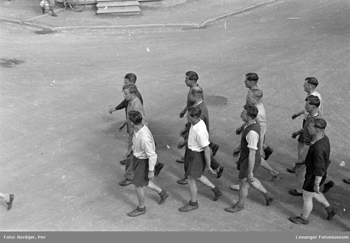 Gatescene tatt fra 2 etasje fra vindu,  en gruppe menn ute og trener, trolig tyske soldater i sivil.