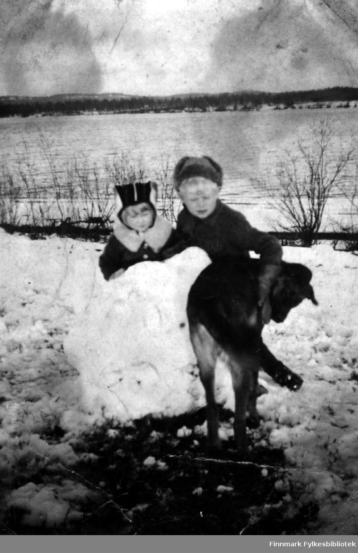 Fotografi av Mirjam og Eero Ranta. På bildet står de bak en stor snøklump. Det står en hund foran dem, som Eero holder armen sin på. Begge barna er kledt i luer og jakker. Mirjam har en krage rundt halsen. Det ligger snø på bakken i bakgrunnen ser man skog på andre siden av elven som er isfri