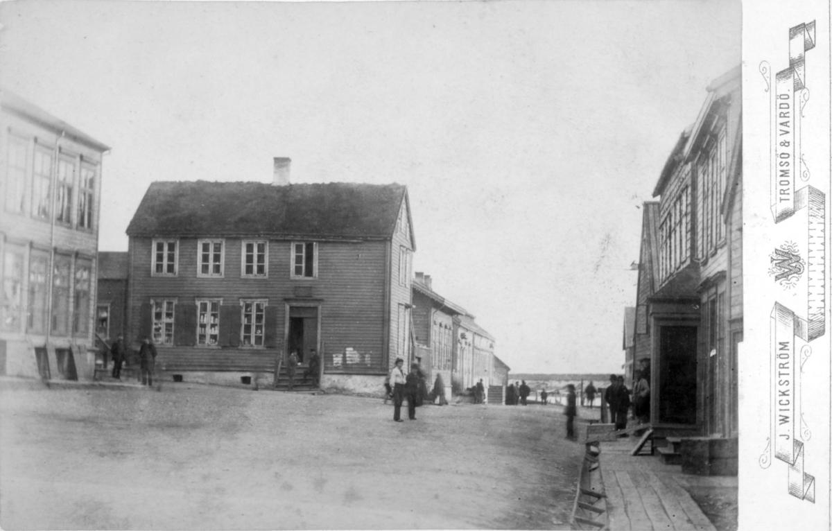 Torget og Tollbodgaten i Vadsø fotografert mot sør. Vi ser butikker, mennesker og Vadsøya i bakgrunnen. Legg merke til plankefortauene