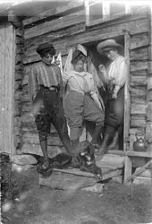 Tre kvinner poserer i en døråpningen til et tømmerhus, iført