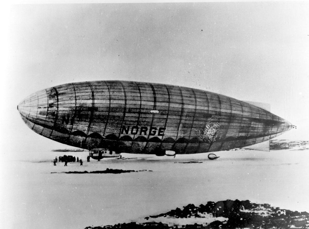 """Luftskipet """"Norge"""" fortøyd ved bakken. Flere personer ved luftskipet. Snø."""