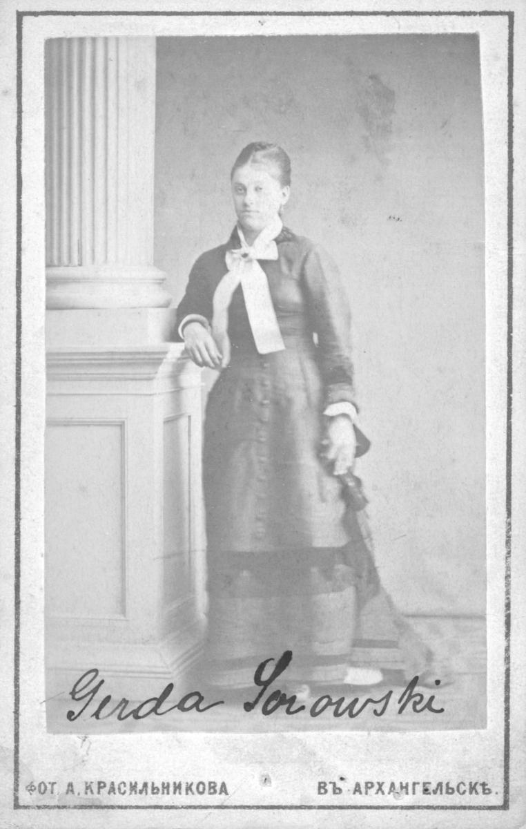 Portrett av en ung kvinne ved navn Gerda Sorowski, fra Arkhangelsk i Russland. Bildet kan være tatt rundt ca. 1860, muligens tidligere. Kvinnen står ved en søyle i et fotoatelier. Hun bærer en mørk kjole med hvit krage og en stor hvit sløyfe i halsen som er holdt på plass med en nål. I hånden holder hun en liten vifte. Det annet portrett, FBib. 96009-053, viser samme atelier, men en annen kvinne i samme stil.