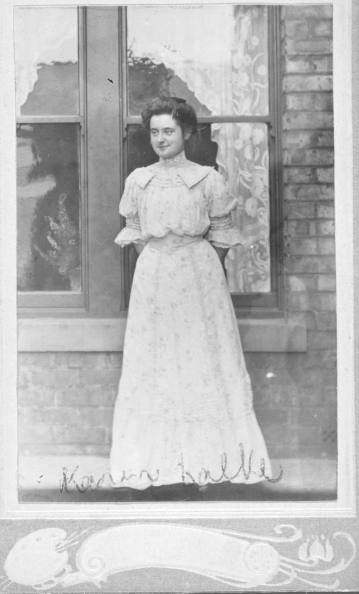 Portrett av en ung kvinne, Karen Balke. Karen er fotografert mot en husvegg i murstein. Hun er kledt i en lang blomstrete sommerkjole. I bakgrunnen skimter man også et vindu med blondegardiner og potteplanter. I Digitalarkivet er hun oppført som Karen L. Balke, født i Karasjok i 1886. I folketellingen for 1900 er hun registrert som skoleelev og bor i Vadsø.   Hennes far er sogneprest J.M. Balke, født i Kristiania i 1854 og mor er Thora Balke. Thora Balke er født i Moss i 1857. J.M. Georg Balke var sogneprest i Vadsø på denne tiden. Hans fulle navn var Johan Max Georg Balke. Han døde i Bærum 17.mars 1937, 82 år gammel. Sognepresten var sønn av Peder Balke og Karen Balke. Han var altså sønn av maleren Peder Andersen Balke.