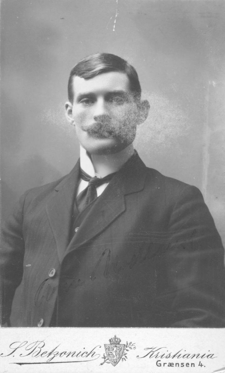 Halvfigur portrett av  Arne Nodland. Han er kledd i dess og slips. Fotografert i Kristiania.