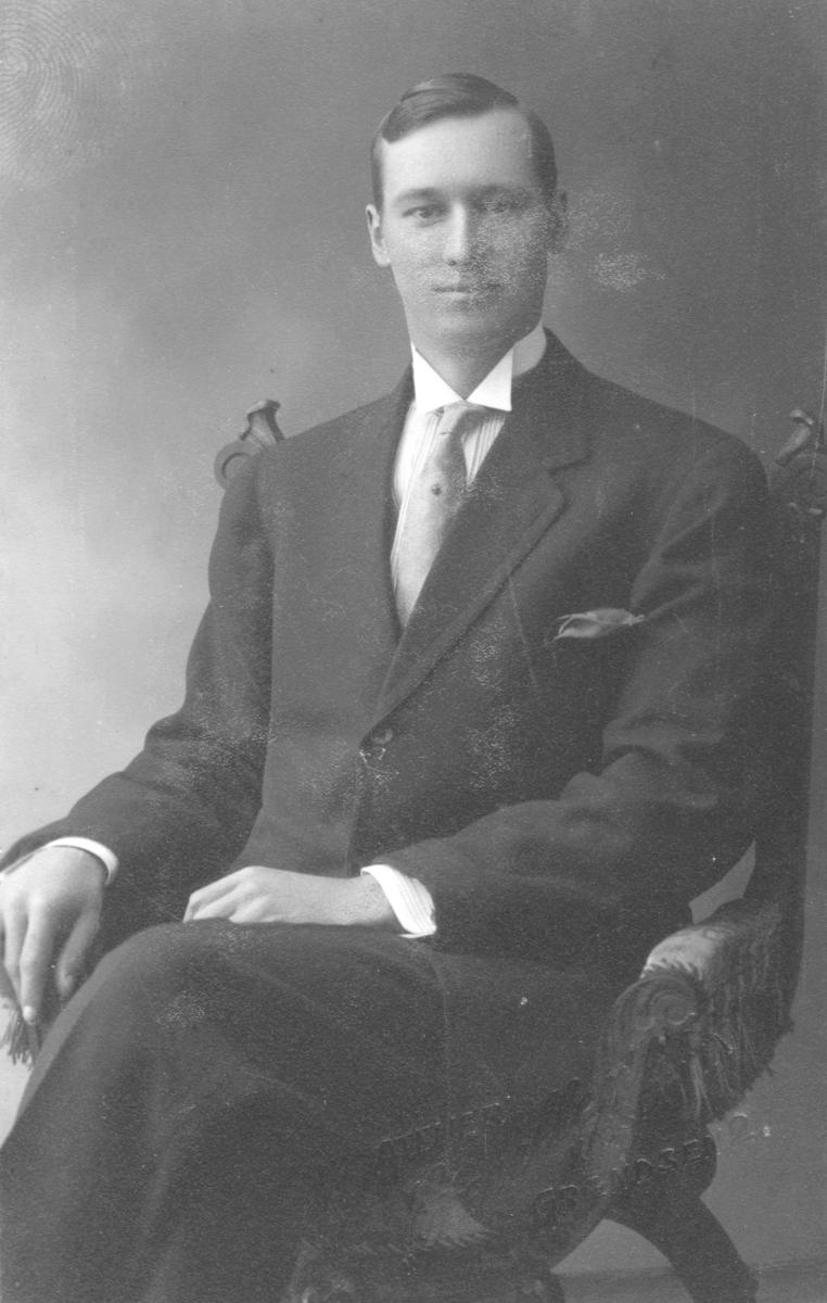 """Portrett av en ung mann. Han er kledd i en mørk og meget stilig dress med skjorte med snipp,  slips med slipsnål og pyntelommetørkle i dressjakkelommen. I albumet står det bare  """"venn av Olga""""."""