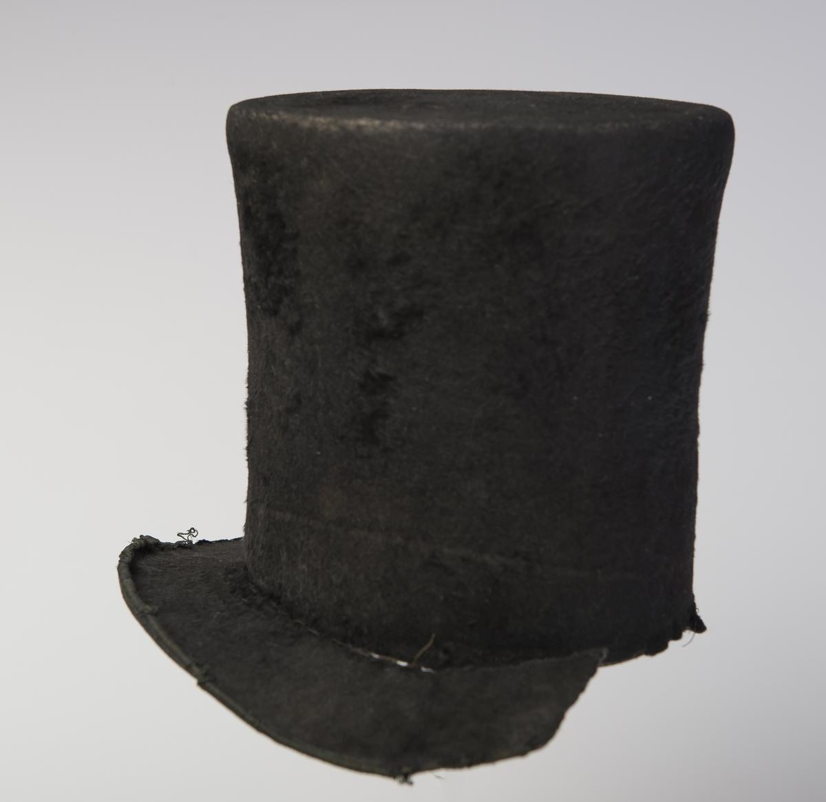 Flosshatt med høy stiv pull som er flat på toppen. Bremmen er flat fram og bak, noe  oppover bøyd på sidene. Bremmen er ødelagt på den ene siden. Ytterkanten av bremmen har påsydd et smalt bånd. Bredt svettebånd  med knyttesnor øvert. Inne i hatten er det et løst for av tyllstoff og papir med uleselig trykk på.