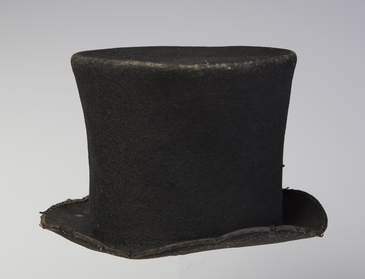 Filthatt med høy stiv pull som er flat på toppen. Bremmen har påsydd et skinnstykke på undersiden av hatten. Ytterkanten av bremmen har påsydd et smalt bånd. Inne i pullen er det et papir med trykk på. Øvre del av hatten har større omkrets enn lenger nede. Denne type hatt er forløperen til flosshatt.