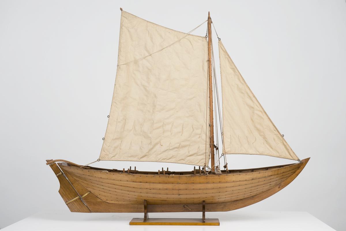 Båtmodell, blekingseka, bordlagd på spant, klink, fullständigt inredd. Riggad med segel. Roder med rorkult. 4 st åror. Fernissad. Stativ fernissat.