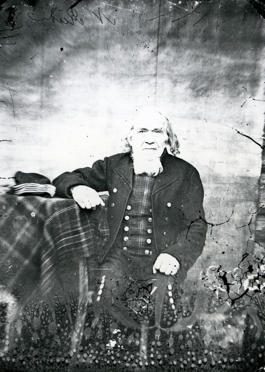 Mann, kledd i tradisjonelle klær, blant annet rutemønstret vest. Sitter ved bord med duk, lue ligger på bordet, lerretbakgrunn