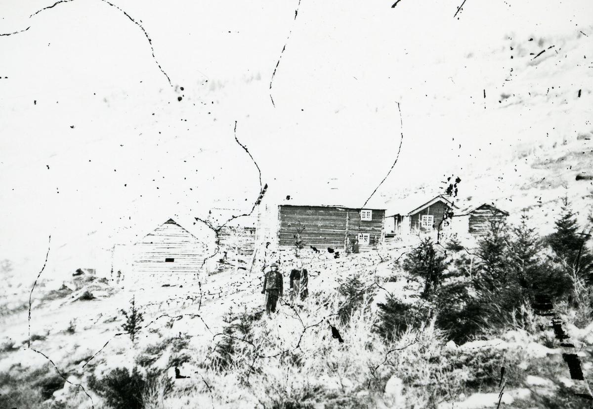 Gård i skrått terreng. Mann og kvinne i framgrunnen, foran steingjerde
