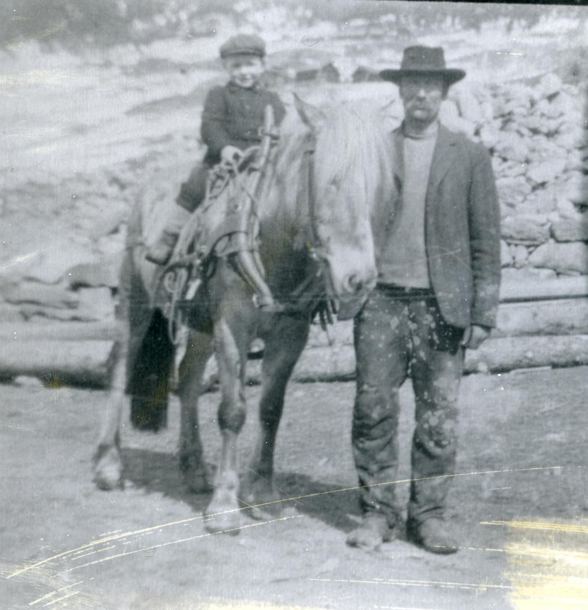 """Arbeidskar og påsæla hest med liten gut sitande på ryggen. Tømmerstokkar og steinhaug i bakgrunnen. """"Trufaste slitarar"""" påskreve ved bildet"""