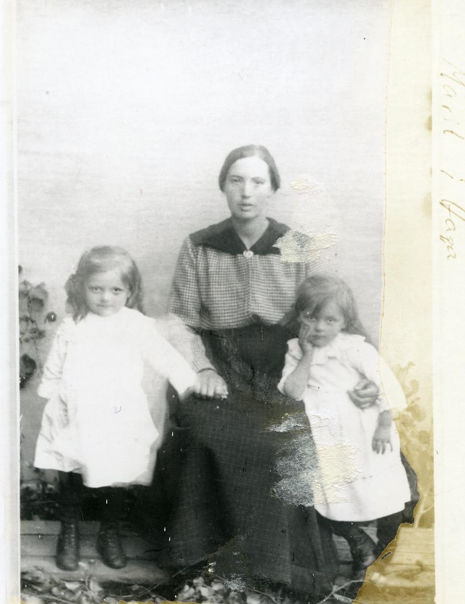 """Sitande kvinne med to små jenter. """"Marit i Haga"""", saman med dei to jentene ho tok til seg, Svanhild og Kristine"""
