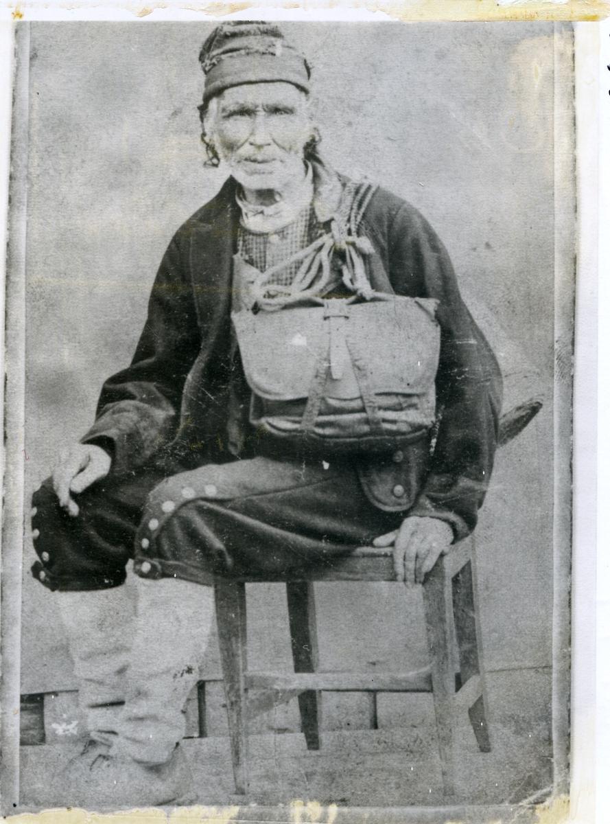 Mann med veske, kledd i noko tradisjonelle klede, sitande på stol