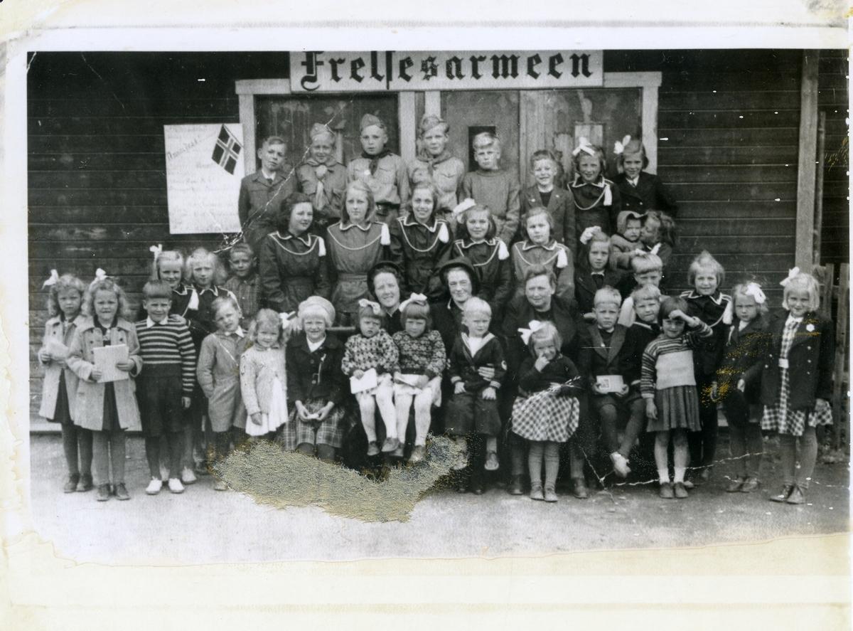 Gruppebilde av elever ved søndagsskolen på Fagernes. Festkledde barn og unge foran huset til frelsesarmeen.