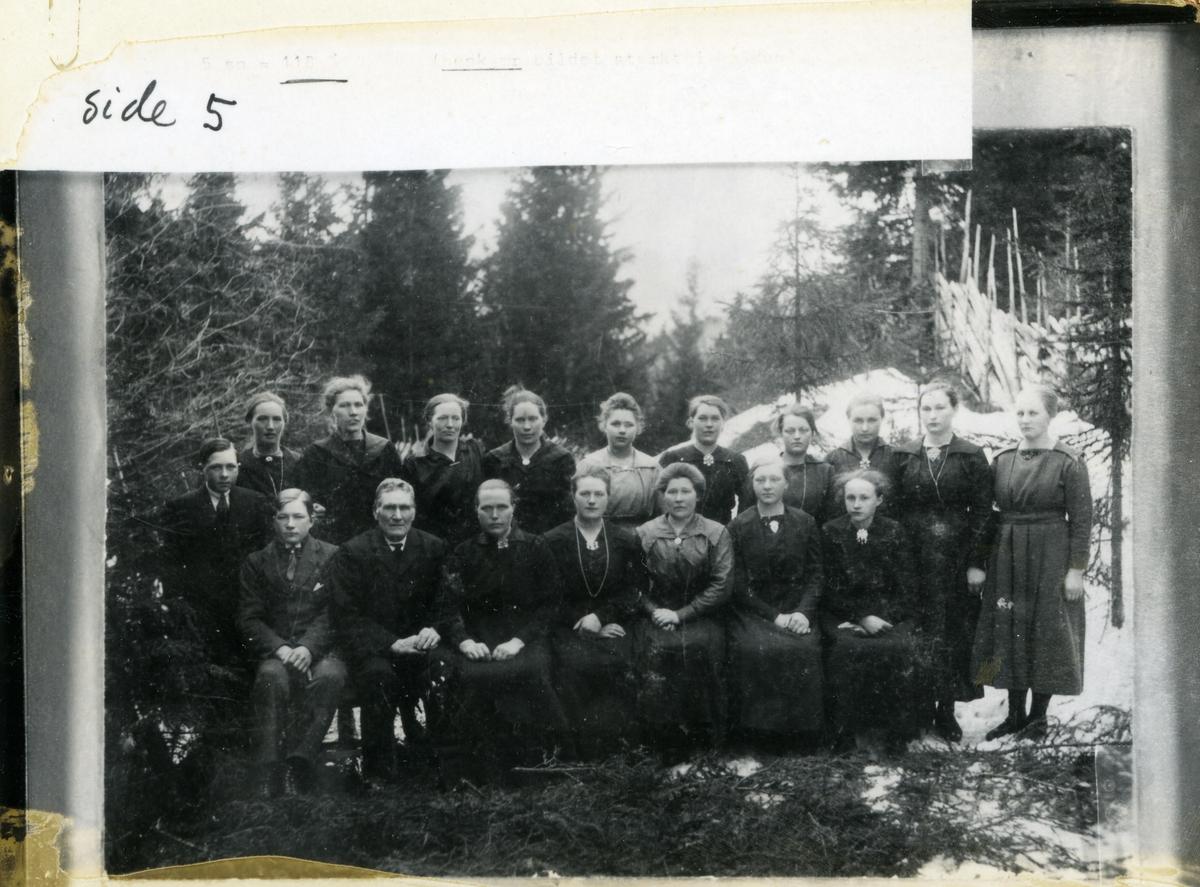 Gruppebilde med elever fra syskole på Kvissel i Lomen. Bildet er tatt ute i vinterhalvåret med skog og skigard i bakgrunnen