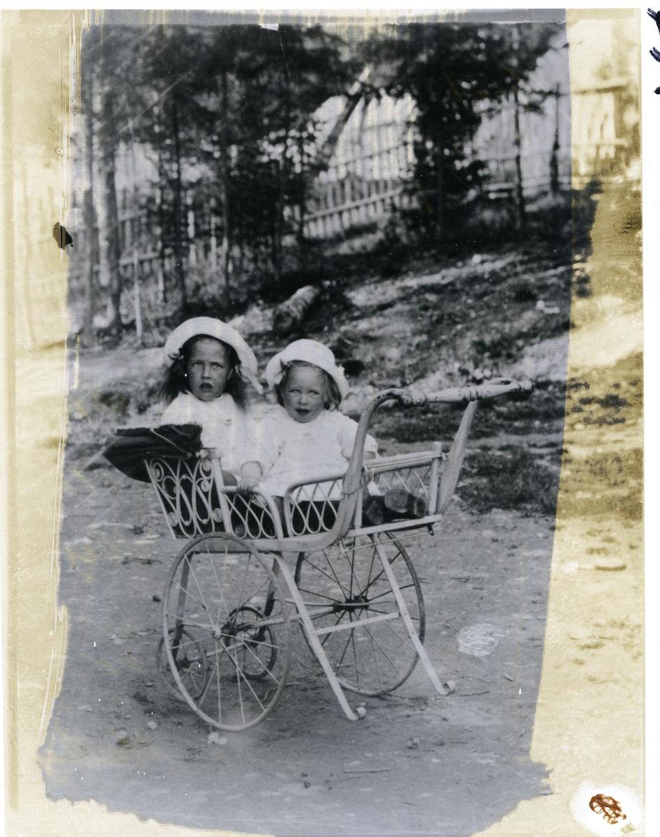 To jenter sittende i barnevogn . Sigrid f. 1915 gift Hall og Synnøve f.1916 gift Kolstad. Bildet er tatt utenfor kjøpmann Melby sin forretning og jentene er hans døtre. Bildet er tatt ca 1917.