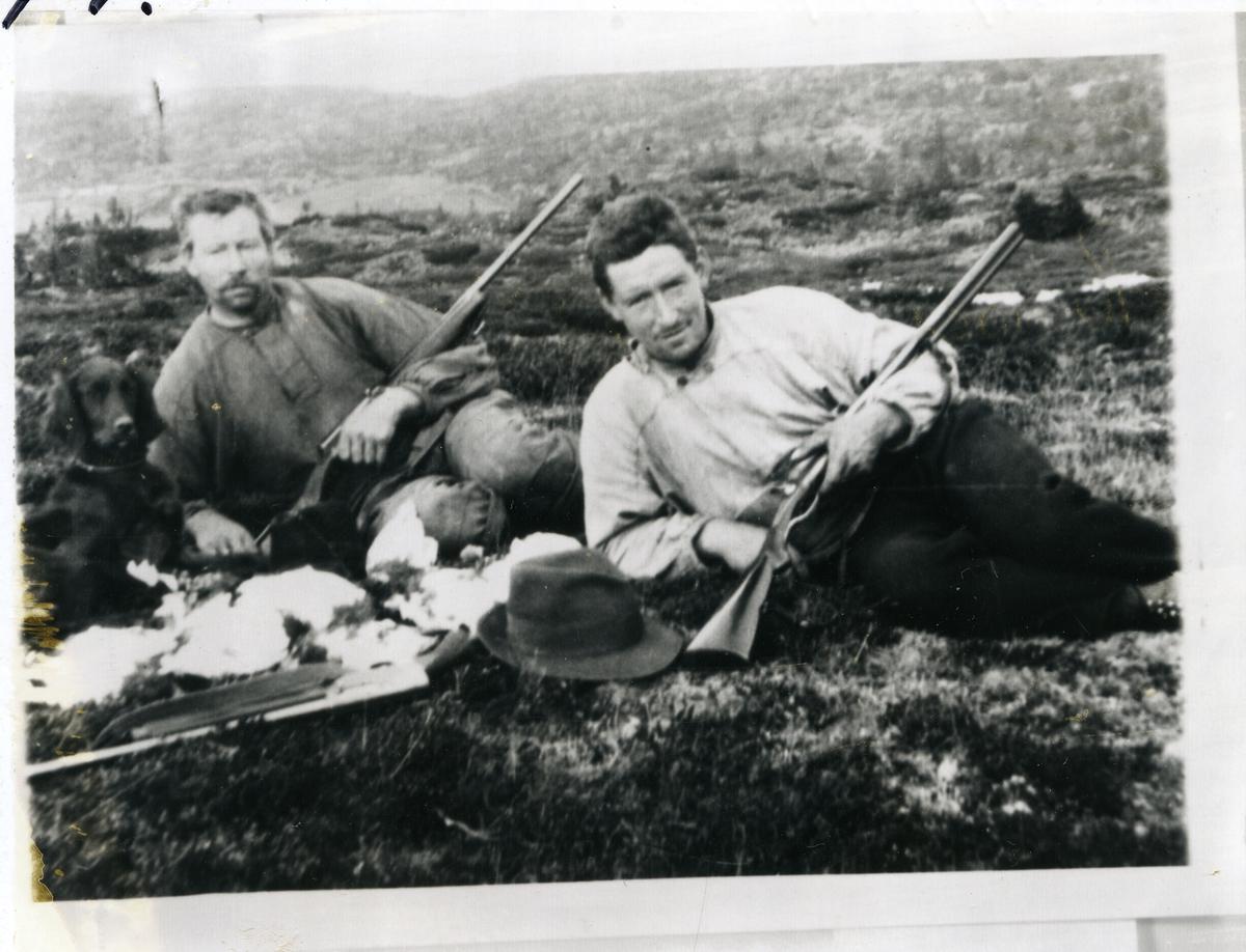 2 menn avbildet sittende på bakken med jaktvåpen i hendene. En hund sitter ved siden av dem og jaktutbyttet, ryper, ligger foran dem. Bildet er tatt på fjellet. Bildet er tatt 1922