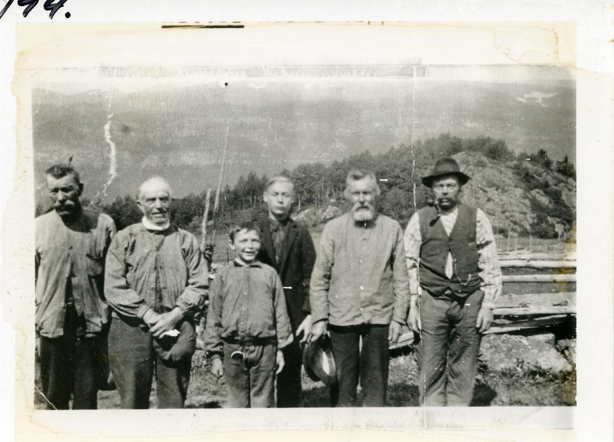4 menn og 2 unge gutter i arbeidsklær. Avbildet ute