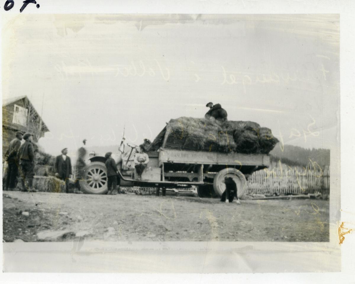 Lastebil med forlass foran stakittgjerde. Tømmerbygning til venstre. Barn, karer og en hund er med på bildet. Jørgen Dale er sjåfør  (1897-1979).Bildet er tatt rundt 1918-1920