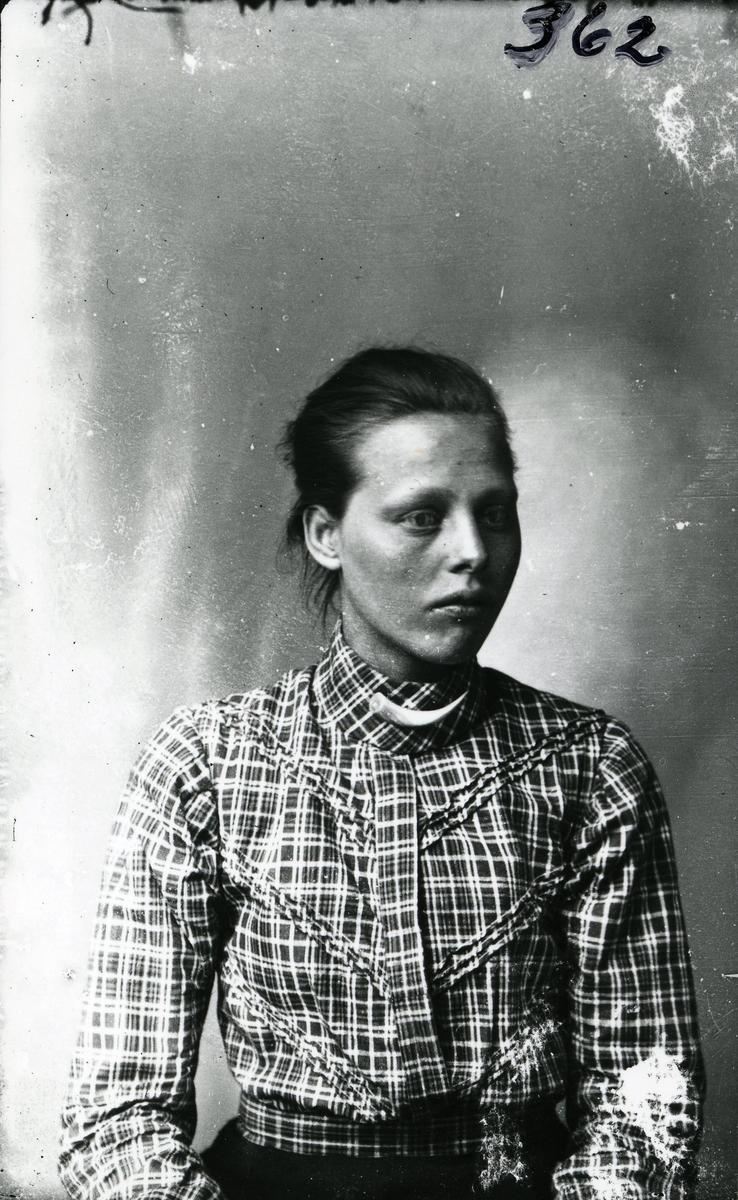 Portrett i halvfigur av kvinne sittende foran lerret. Rutete bluse og svart skjørt.