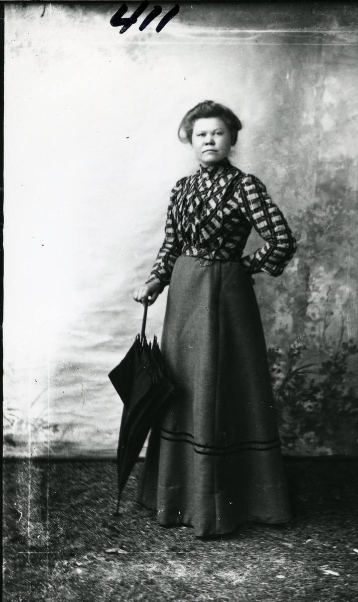 Kvinne i helfigur med lang, mørk stakk og rutete bluse. Paraply. Oppsatt hår og perlebånd rundt halsen